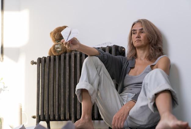 Une femme âgée avec une expression déprimée est assise sur le sol de son appartement