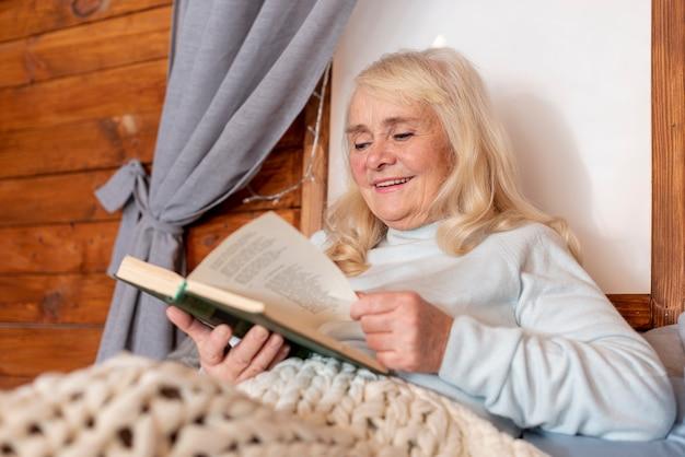 Femme âgée à faible angle au moment de la lecture