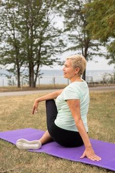 Femme âgée faisant du yoga à l'extérieur dans le parc