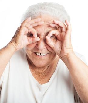 Une femme âgée faisant des lunettes avec ses doigts