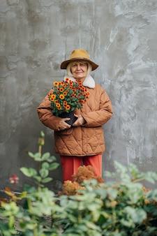 Femme âgée avec des fleurs debout contre le mur. femme senior en vêtements d'extérieur portant des fleurs en pot