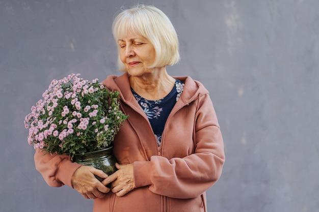 Femme âgée avec des fleurs en pot. femme âgée en hoodie tendance exerçant son pot avec des fleurs fraîches