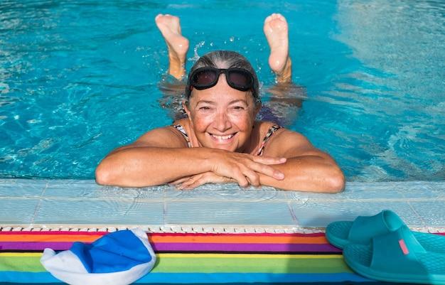 Une femme âgée gaie avec des lunettes de natation profite de l'eau de la piscine. piscine extérieure à l'eau claire. les pieds hors de l'eau. activité saine pour garder la forme. les retraités en lieu tropical