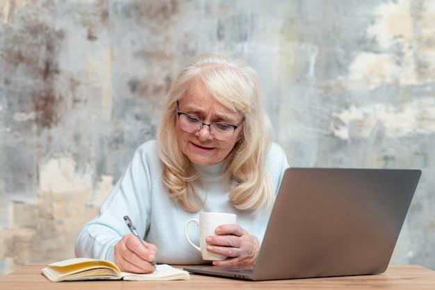 Femme âgée grand angle prenant des notes à l'ordre du jour