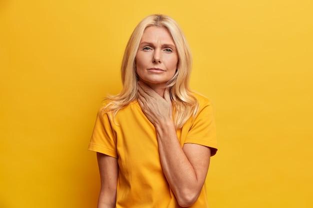 Une femme âgée grave souffre de maux de gorge, touche le cou et grimace de douleur se sent mal en avalant des poses de vêtements décontractés