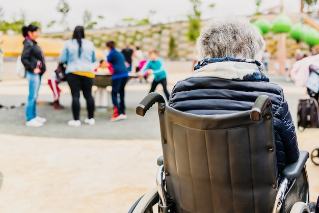 Femme âgée handicapée assise dos à dos dans un fauteuil roulant dans une aire de jeux.
