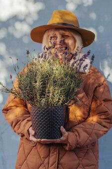 Femme âgée heureuse avec de la lavande en pot. femme âgée joyeuse souriante