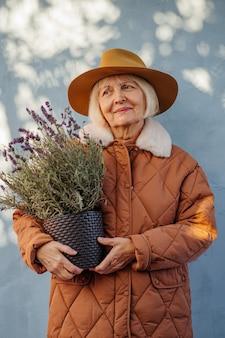 Femme âgée heureuse avec de la lavande en pot. joyeuse femme âgée en vêtements d'extérieur à la mode et chapeau souriant