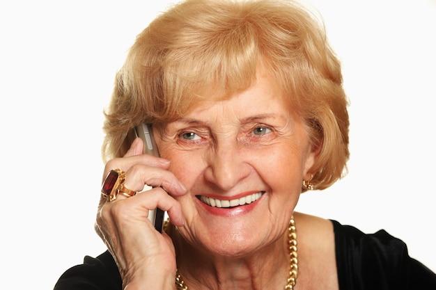 Une femme âgée heureuse parlant au téléphone sur fond blanc