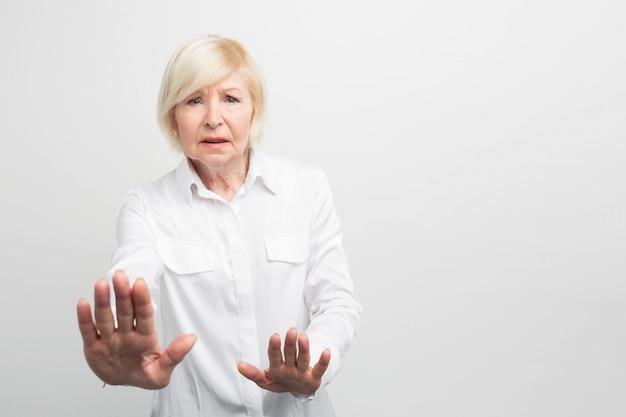 Une femme âgée et inquiète montre qu'elle est assez catégorique. elle est refus. vue en coupe.