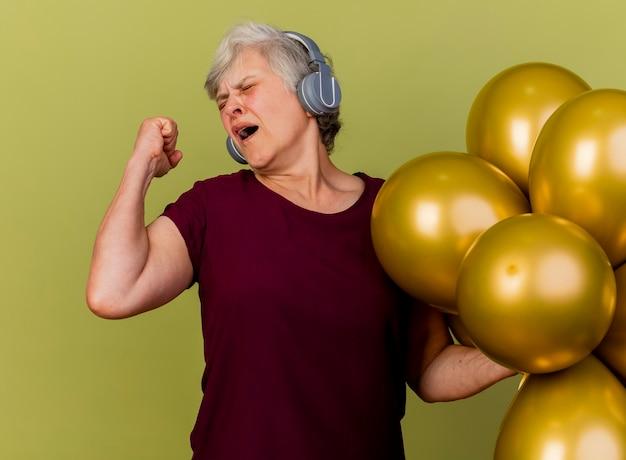 Femme âgée insatisfaite sur le casque se dresse avec des ballons d'hélium gardant le poing isolé sur mur vert olive avec espace copie