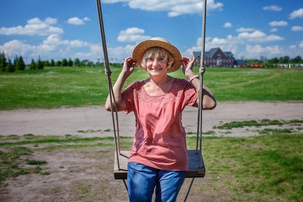 Femme âgée insouciante au chapeau de paille se balançant sur une balançoire en bois génération de baby-boomers de beauté d'âge