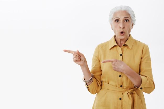 Femme âgée intriguée et étonnée posant des questions et pointant vers la gauche curieuse