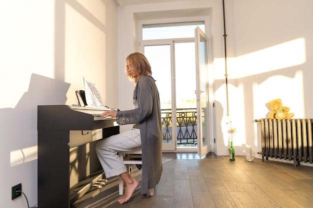 Une femme âgée joue du piano électronique dans une pièce à travers les fenêtres de laquelle bat la lumière du soleil