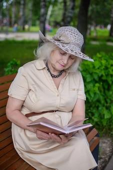 Une femme âgée lit un livre dans le parc