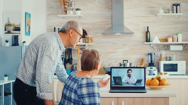 Femme âgée lors d'une vidéoconférence avec un médecin montrant une bouteille de pilules. consultation de santé en ligne pour personnes âgées médicaments conseils sur les symptômes, webcam de télémédecine du médecin. stagiaire en soins médicaux
