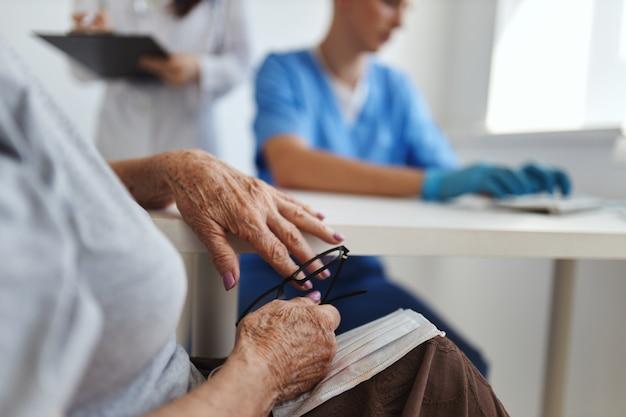 Une femme âgée avec des lunettes dans les mains assise à un service de rendez-vous chez les médecins