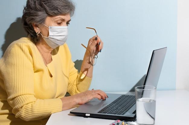 Femme âgée avec des lunettes et un masque médical à l'aide d'un ordinateur portable à la maison. concept de consultation en ligne avec un médecin, recherche sur internet, auto-isolement, nouvelle normalité.
