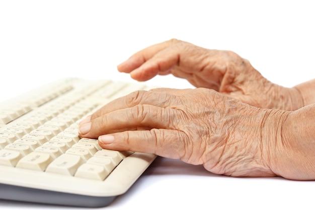 Femme âgée les mains sur le clavier de l'ordinateur