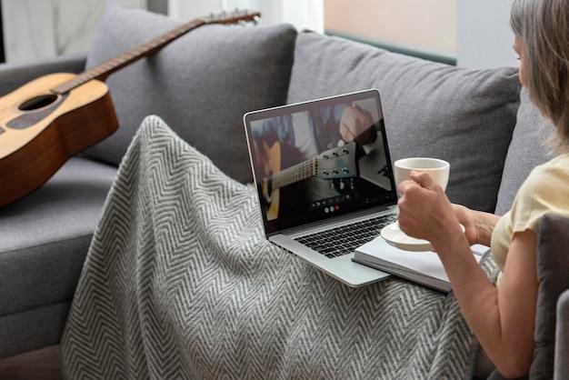 Femme âgée à la maison sur le canapé à l'aide d'un ordinateur portable et prenant un café
