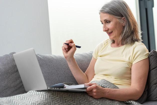 Femme âgée à la maison sur le canapé à l'aide d'un ordinateur portable et prenant des notes
