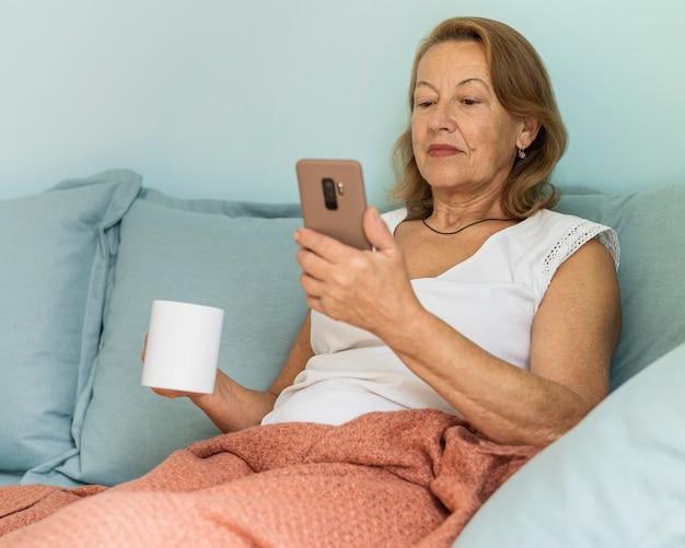 Femme âgée à la maison pendant la pandémie en dégustant une tasse de café et à l'aide de smartphone