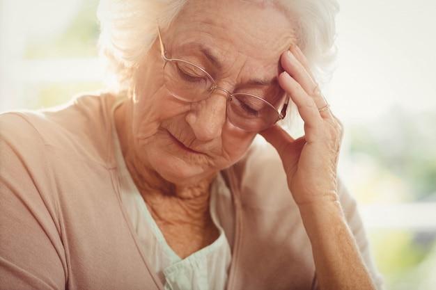 Femme âgée avec mal de tête à la maison