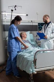Femme âgée malade recevant des médicaments par voie intraveineuse, allongée dans un lit d'hôpital
