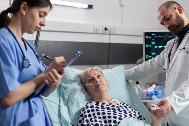Femme âgée malade regardant le personnel médical allongé dans un lit d'hôpital avec un masque à oxygène pour l'aider à inspirer et à expirer