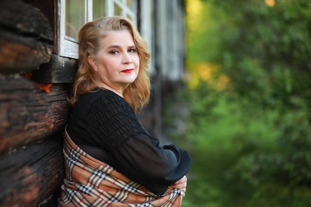 Une femme âgée avec un maquillage de soirée sur le porche d'une maison de campagne