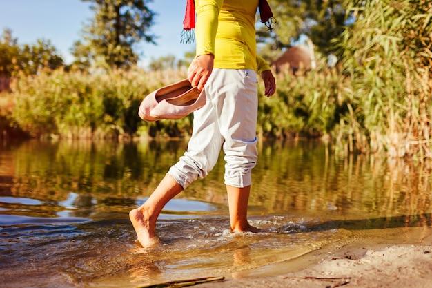 Femme âgée marchant sur la berge le jour de l'automne senior dame s'amusant