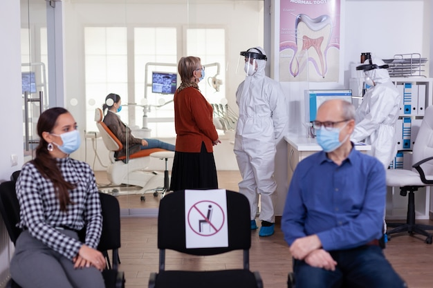 Femme âgée avec masque facial discutant avec un dentiste vêtu d'un costume de ppe dans une clinique de stomatologie, par mesure de sécurité pendant la pandémie mondiale de coronavirus