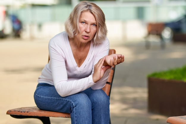 Une femme âgée mesure sa fréquence cardiaque assise sur un banc dans la rue.