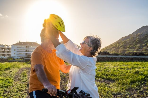 Une femme âgée met un casque de protection sur son mari pour faire du vélo. lumière vive du coucher du soleil