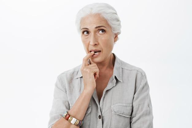 Femme âgée mignonne réfléchie et rêveuse mordre le doigt et à la recherche dans le coin supérieur droit