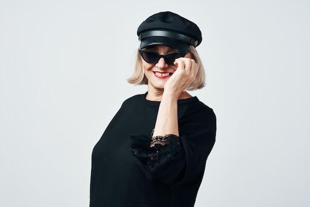 Femme âgée à la mode portant des lunettes de soleil posant en gros plan