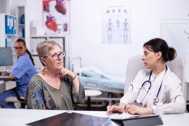 Femme âgée montrant au médecin un mal de gorge lors d'une consultation médicale assise dans une chambre d'hôpital. patient âgé visitant un médecin examinant la gorge thyroïdienne touchant la santé à la clinique, traitement médical
