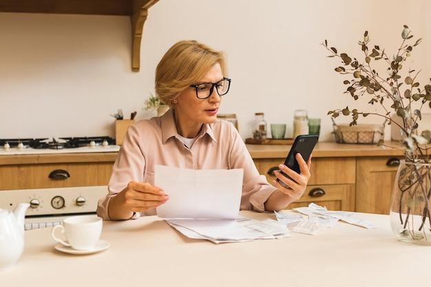 Femme âgée mûre d'âge moyen tenant une facture papier ou une lettre à la maison pour effectuer des paiements en ligne sur un site web sur un téléphone mobile, calculer le coût des taxes financières, examiner le compte bancaire.