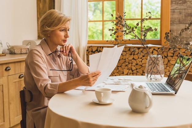 Femme âgée mûre d'âge moyen tenant une facture papier ou une lettre utilisant un ordinateur portable à la maison pour effectuer des paiements en ligne sur le site web, calculer le coût des taxes financières, examiner le compte bancaire.