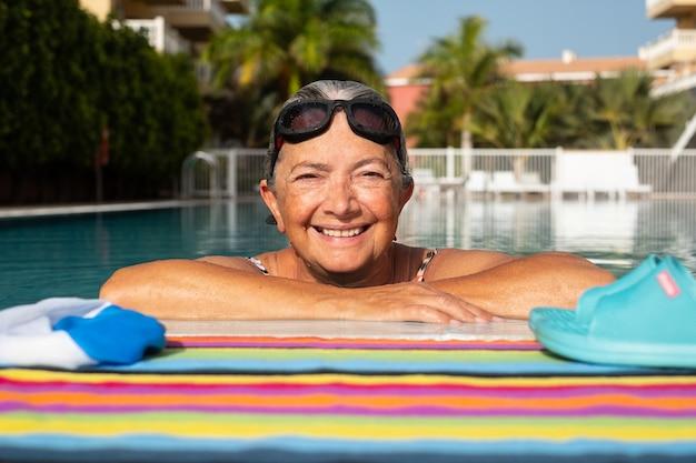 Une femme âgée nageant dans une piscine extérieure. concept de vacances et de temps libre