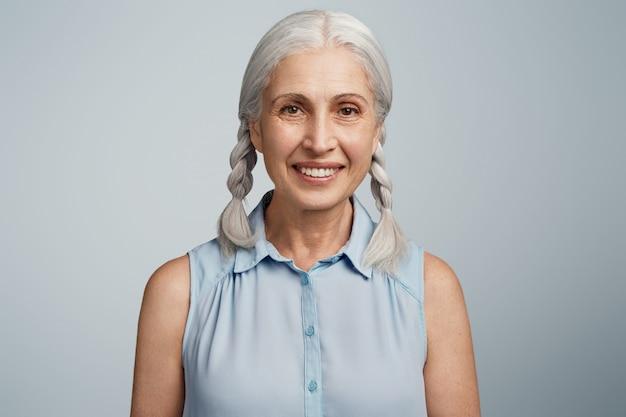 Femme âgée avec des nattes posant