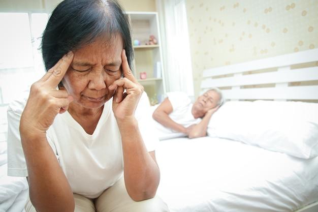 Une femme âgée ne peut pas dormir souffre de stress, de problèmes de santé et de sautes d'humeur. concepts d'aide à l'aîné ayant des problèmes de santé mentale