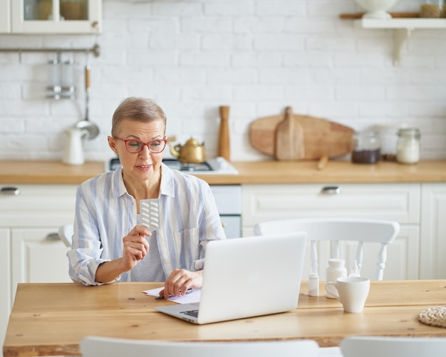 Femme âgée parlant en ligne avec un médecin pendant la covid alors qu'elle était assise dans la cuisine à la maison
