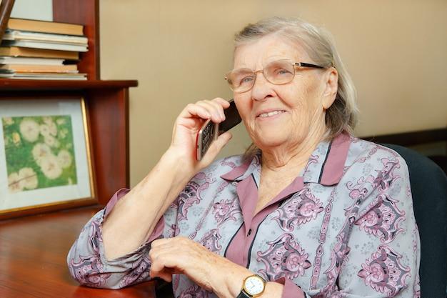 Femme âgée, parler téléphone portable, chez soi, et, sourire