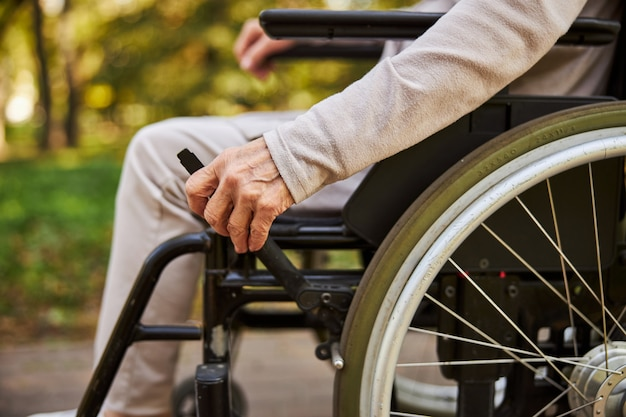 Une femme âgée part en appuyant sur une poignée de son fauteuil roulant