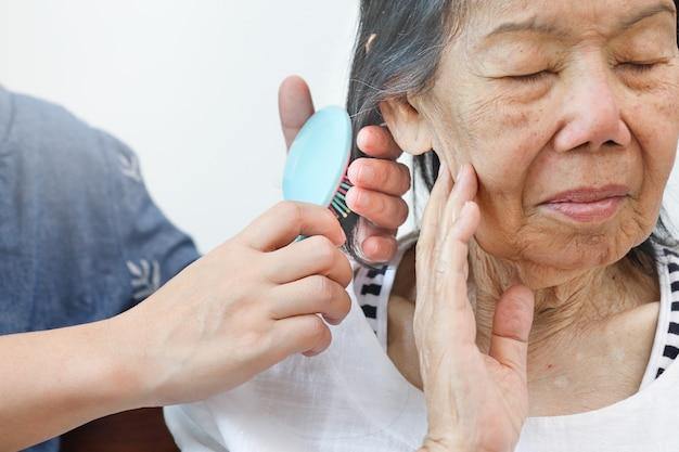 Femme âgée, peigner les cheveux, par, soignant
