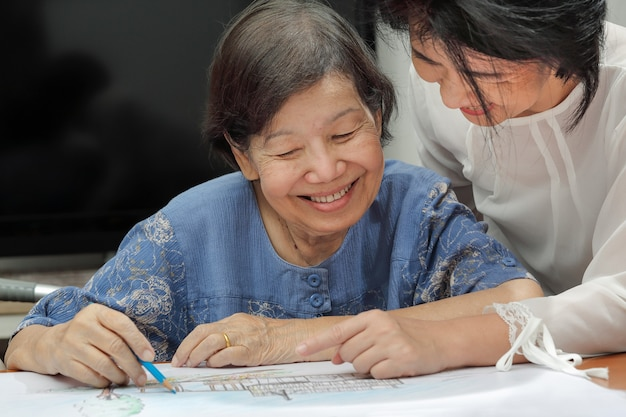 Femme âgée peinture couleur sur son dessin avec sa fille, passe-temps à la maison