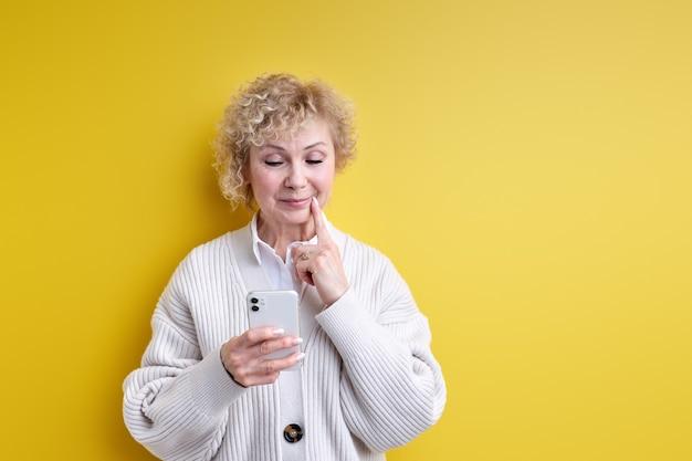 Femme âgée pensant tout en discutant avec quelqu'un au téléphone, tenant un smartphone moderne dans les mains, touchant le menton. isolé