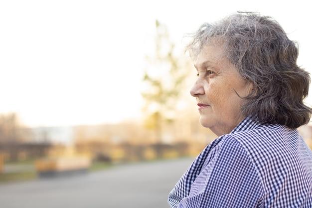 Une femme âgée pensive regarde sur le côté. visage de profil. grand-mère aux cheveux gris.
