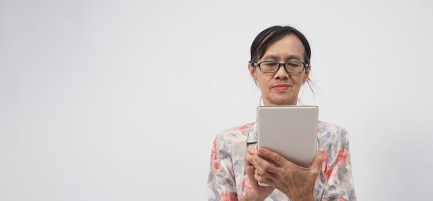 Une femme âgée ou plus âgée utilise un smartphone ou une tablette sur fond blanc.